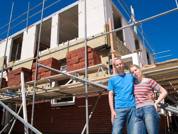 Couple outside house build